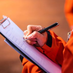 Photo of Prevention Officer hand writing note on a clipboard