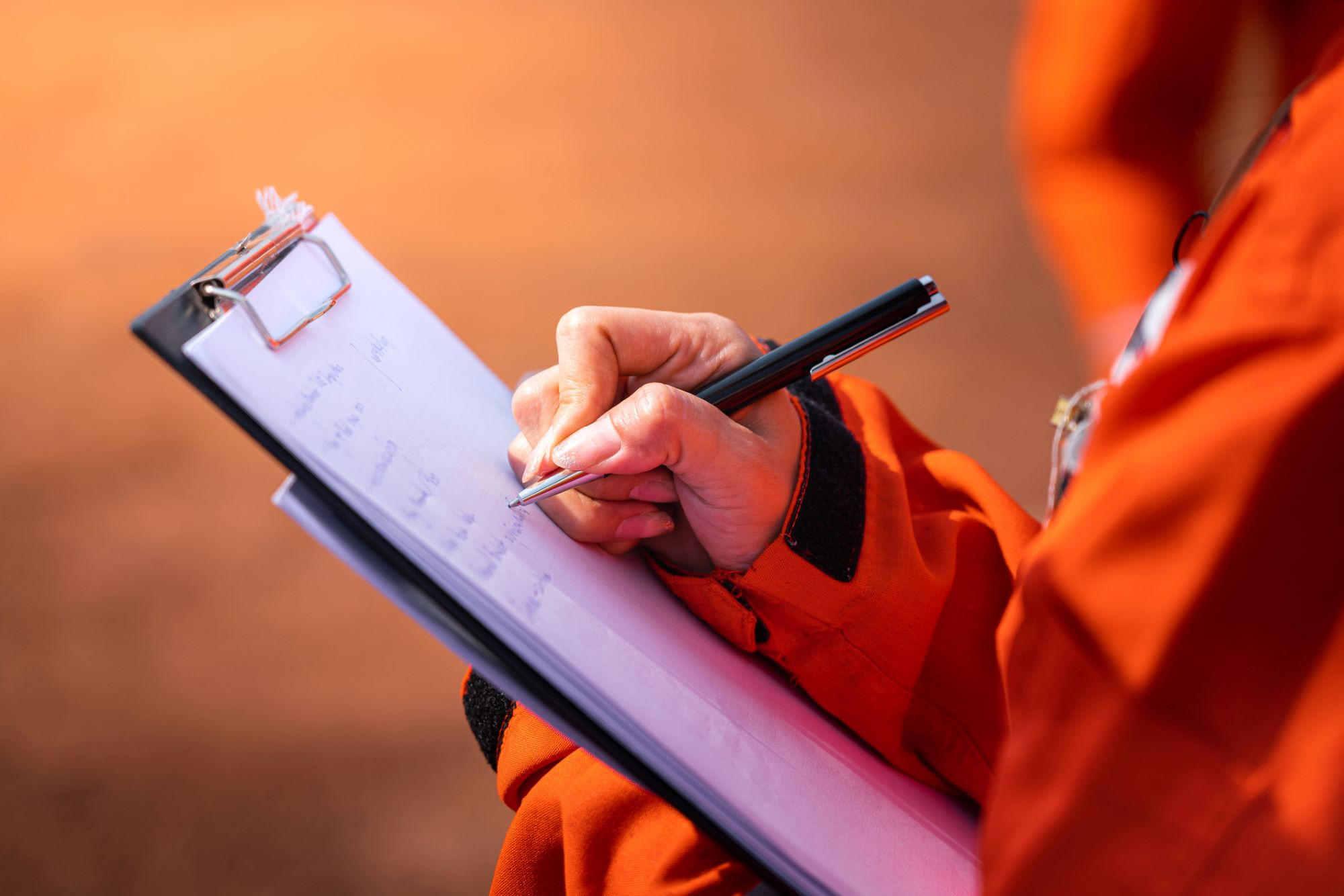 Photo of Prevention Officer writing note on the checklist paper of a clipboard