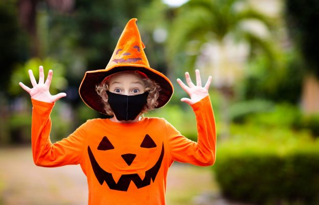 Photo of boy wearing Halloween costume and face mask during COVID-19 pandemic