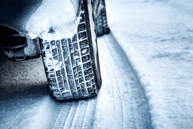 Photo of a rear winter tire of a car driving on a snow covered road
