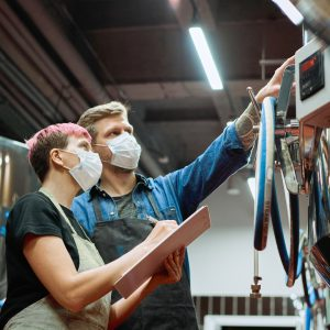 Photo of young worker and employer looking at a control panel while working at a brewery.