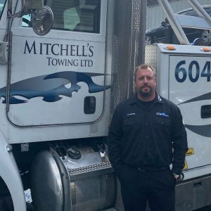 Photo of Mitchell Martin, tow truck driver and owner of Mitchell's Towing, standing at the door of his tow truck.