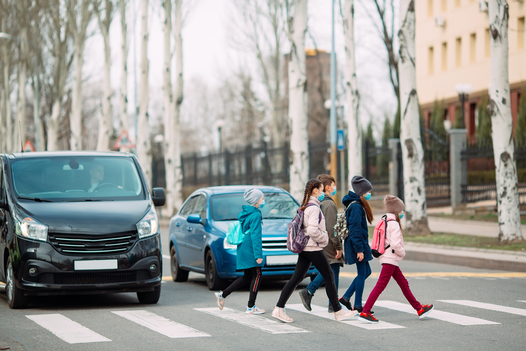 Photo of school children crossing the road while cars are stopped.