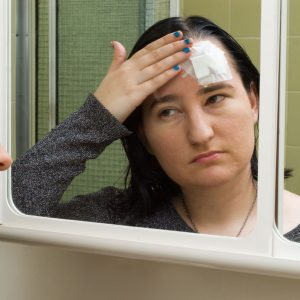 Photo of a young woman checking her head injury in the bathroom mirror.