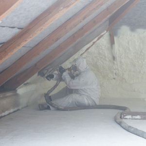 Photo of technician spraying foam insulation using plural component gun for polyurethane foam, inside