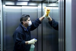 Photo of cleaning staff reaching as they disinfect elevator to avoid contagion