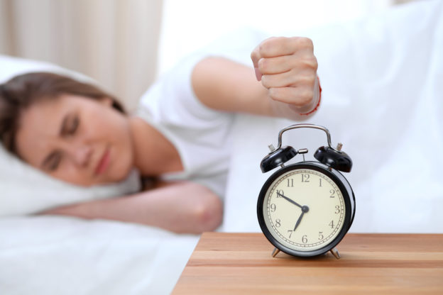 Photo of woman in bed reaching fist toward alarm clock