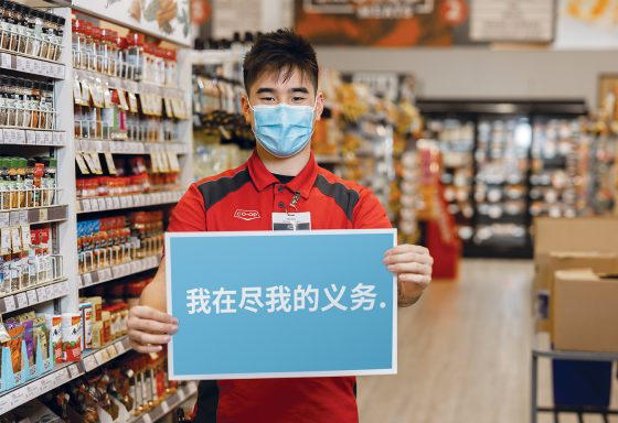 """Photo of person wearing non-medical face mask and holding sign in Mandarin """"I'm doing my part"""""""