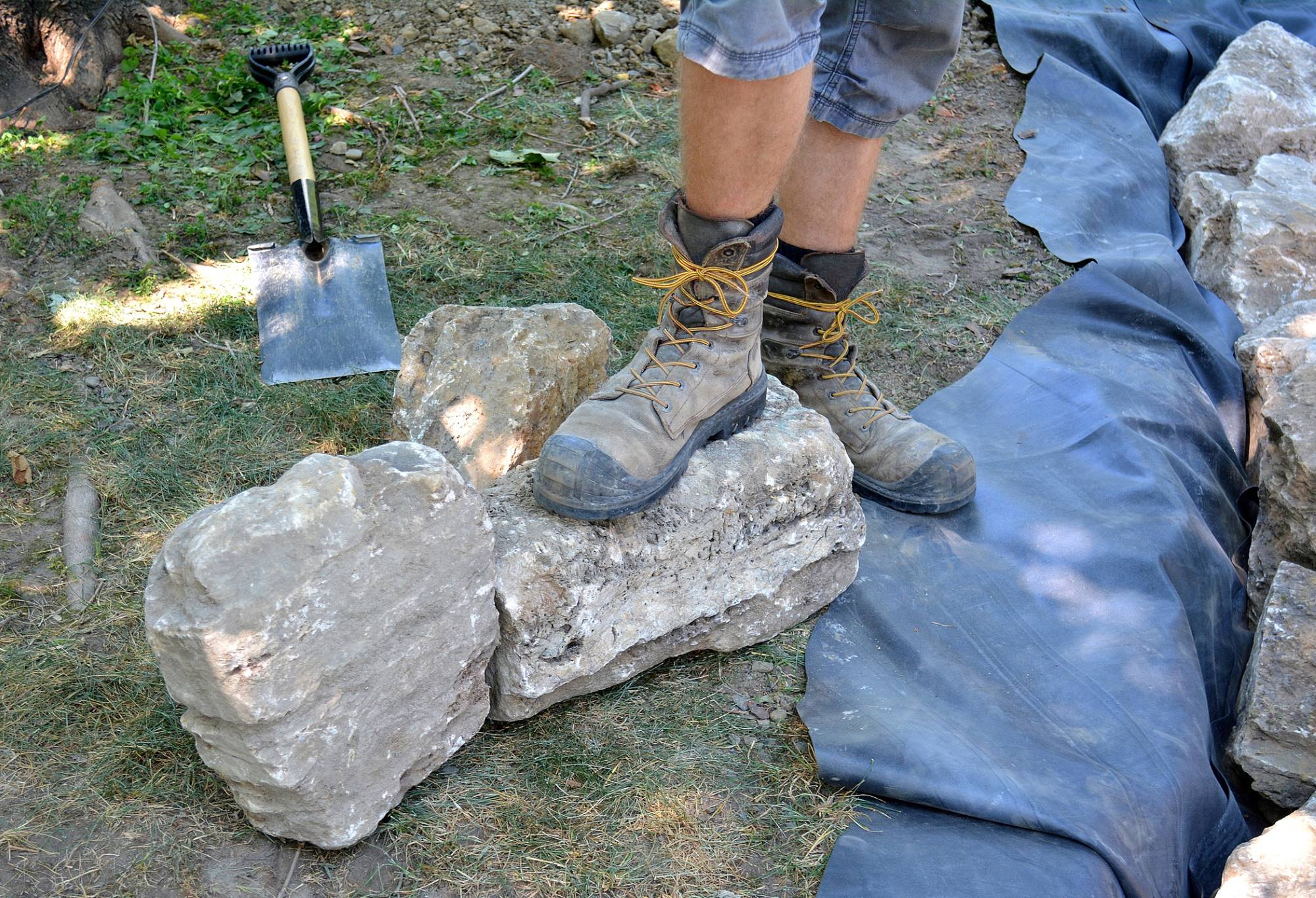 Photo of feet and work boots of a construction worker, with some decorative stone and equipment, that they will use for a landscaping project.