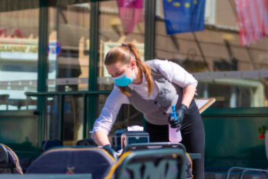 Photo of a coffee shop worker cleaning a table while wearing a surgical mask and protective gloves to prevent spread of COVID-19 transmission.