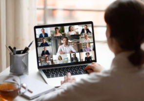 Photo of a person looking at people on a video-conferencing message.