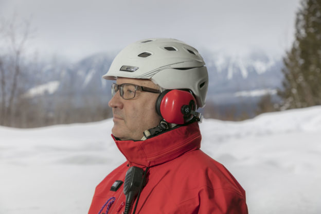 Photo of a ski guide wearing behind-the-head earmuffs, along with a helmet