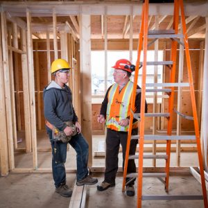 Photo of two workers talking in a in a room under construction with only wood beams.