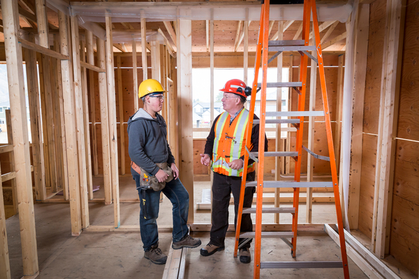 Photo of two workers talking in a room under construction with only wood beams.