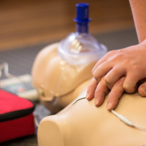 Photo of hands on chest of CPR maniken as person practices chest compressions